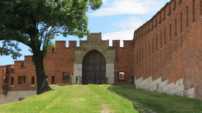 Castle Gate. Ramp up to a castle gate with brick walls and large wooden gate Royalty Free Stock Image