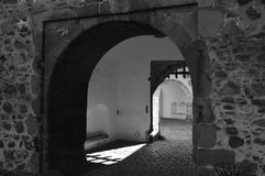 Castle gateway. Falling door in backdrop. Small gate in black and white view. On background are falling wooden doors. Middle Europe. Stone walls. Medieval Royalty Free Stock Photos