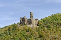 Castle on Hill. A historical medieval castle on a steep rocky forest covered hill that is a favorite tourist destination location in Germany on the River Rhine royalty free stock photography
