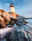 Castle Hill Lighthouse Newport Rhode Island at Sunset. Small Castle Hill Lighthouse sits on the rocky coastline of Newport, Rhode Island at sunset with the waves Royalty Free Stock Photos