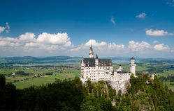 Castle on a hill with a view. Bavarian castle Neuschwanstein in a summer royalty free stock photo