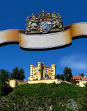 Castle Hohenschwangau, Germany. Castle Hohenschwangau (#2) from under the banner of a Beer Garden in the vicinity featuring the Bavaria's coats of arms. The site Royalty Free Stock Photography