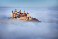Castle Hohenzollern over the Clouds. Castle Hohenzollern in the south of Germany in Autumn in the Morning. The castle looks through the Fog Royalty Free Stock Photo