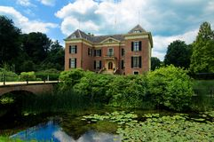 Castle Huis Doorn Netherlands. Castle Huis Doorn Surrounded with Beautiful Pink Water Lilies between Leafs and Sky Reflection on Water closeup Outdoors. Utrecht Royalty Free Stock Photos