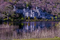 Castle in irlande at the edge of a lake of connemara stock image