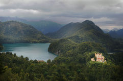 Castle by lake in forest mountain peaks. Hohenschwangau castle in bavaria Germany on forest hills with mountain peaks overcast day Stock Images