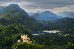 Castle by lake in forest mountain peaks. Hohenschwangau castle in bavaria on forest hills with mountain peaks overcast day Stock Image