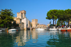 Castle on lake Garda in Sirmione, Italy. Scaliger Castle reflecting in water of lake Garda, Sirmione, Italy Stock Photo