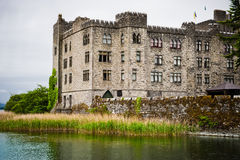 Castle by lake on gloomy rainy day , Ireland Stock Photos