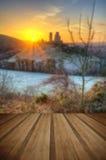 Castle in landscape Winter sunrise with wooden planks floor Stock Image
