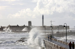 Castle and lighthouse in rough sea, Cadiz Stock Photo
