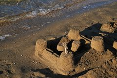Castle made of sand on Croatian beach with tide visible. Stock Photo