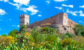 The castle Malaspina above the village of Bosa on a sunny day - Sardinia. Ancient, antique, architecture, bricks, buildings, cross, effect, facade, hill stock image