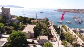 Castle marina aerial yacht Turkish flag drone shot business boat harbor luxury tourism coastline travel Bodrum Mugla, Turkey stock video