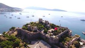 Castle marina aerial yacht Turkish flag drone shot business boat harbor luxury tourism coastline travel Bodrum Mugla, Turkey stock video footage