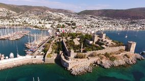 Castle marina aerial yacht Turkish flag drone shot business boat harbor luxury tourism coastline travel Bodrum Mugla, Turkey