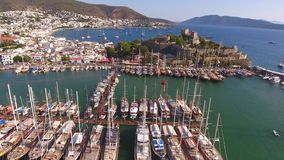 Castle marina aerial yacht Turkish flag drone shot business boat harbor luxury tourism coastline travel Bodrum Mugla, Turkey stock footage