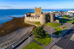 Castle and marina in Carrickfergus near Belfast. Medieval Norman Castle in Carrickfergus near Belfast in morning light. Aerial view with marina, yachts, parking Royalty Free Stock Photo