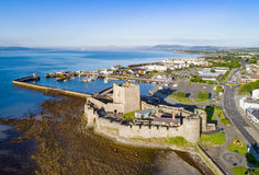 Castle and marina in Carrickfergus near Belfast. Medieval Norman Castle in Carrickfergus near Belfast in sunrise light. Aerial view with marina, yachts, parking Stock Images