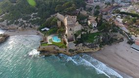 Castle of the Marquises of Tamarit at Tarragona`s beach Spain. A medieval castle with romanesque style on a small promontory overlooking the sea and dated of stock footage