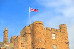 Castle of Mey tower. Close up of the tower of the Castle of Mey with british flag located on north coast of the Highlands in Scotland, United Kingdom on a blue stock images