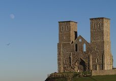 Castle and moon. Reculver Castle and Fort in the early evening light with Moon & bird in the background Stock Image