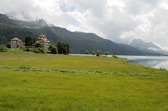 Castle on mountain lake shore, engadin Stock Photos