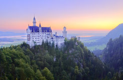 Castle Neuschwanstein. Famous castle Neuschwanstein in Germany on sunrise Royalty Free Stock Images