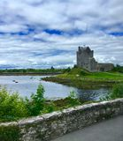 Castle Next to Lake. Very old Irish castle stands proudly for centuries next to a lake. The stone castle green grass, and blue lake make a picturesque setting royalty free stock images