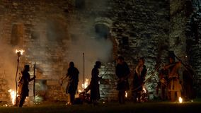 """Castle Night Attack Fire Arrows. Archers launch fire arrows in the medieval castle at night during the reenactment """"Camunerie"""", 11 August 2018, Breno"""