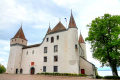 Castle Nyon. Five towered white fairy tale castle Nyon standing on a lake geneva Stock Photos