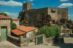 Castle and old houses encircling square with pillory. Sortelha, Portugal - July 20, 2018. Stone Castle with tower over rocky hill and square with pillory at stock photos