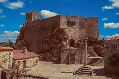 Castle and old houses encircling square with pillory royalty free stock photo