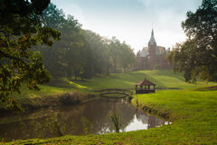Castle in a park. Picturesque castle on a hill by a pond in a park Stock Photography