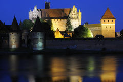 Castle in Poland malbork night. Castle malbork photographed at night with deep blue sky and colored lights reflected in the water of the river Nogat Royalty Free Stock Photos