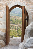 Castle portal. View through ancient wooden doorway of a sunny scene with valley and rocks Royalty Free Stock Image