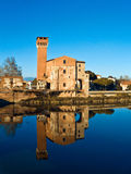 Castle reflected in the Arno river. Pisa, the old ruins of the castel reflected on the blue water of the Arno river royalty free stock images