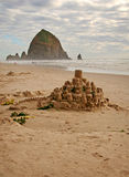 Castle and Rock. Sand castle mirroring the rock at the background Stock Photo