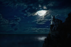 Castle on the rock. Night seascape with the moon and the castle on the hill royalty free stock photos