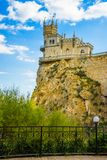 Castle on a rock. Swallow`s Nest. Attractions of Yalta. Alupka. Crimea. View from a walking trail with a black fence, green grass and a white lantern stock photo