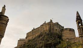 Castle Rock y Edimburgo se escudan, visto de debajo y enmarcado por una chimenea y un chapitel Fotos de archivo libres de regalías