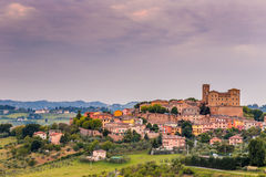 Castle and roofs. Imposing castle and roofs of colored houses brighten the tranquility of a medieval village in the hills of Romagna in Italy stock images