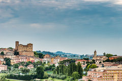 Castle and roofs. Imposing castle and roofs of colored houses brighten the tranquility of a medieval village in the hills of Romagna in Italy royalty free stock image