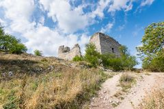 Castle ruin on the hill, blue sky and white clouds, path on the ground Stock Photography
