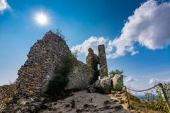 Castle ruin on the hill, blue sky and white clouds, path on the ground Royalty Free Stock Photos