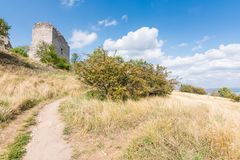 Castle ruin on the hill, blue sky and white clouds, path on the ground stock photos