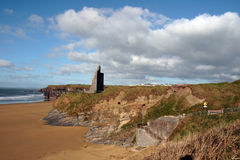 Castle ruins on cliffs above beach Stock Images