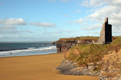Castle ruins on cliffs above beautiful beach royalty free stock image