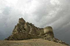 Castle ruins high on the hill. Ruins of a collapsing castle standing alone on the top of a hill stock photos
