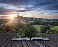Castle ruins landscape at sunrise with inspirational sunburst be. Castle ruins landscape at sunrise with sunburst behind castle conceptual book image Royalty Free Stock Image